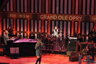 "Lauren Alaina, an American Idol runner-up, is shown performing at Grand Ole Opry with her new song, ""Georgia Peaches"" and her rendition of Loretta Lynn's ""You Ain't Women Enough To Take My Man."""